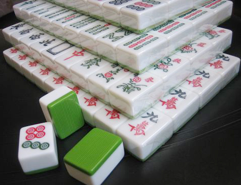 双色麻将牌正面为白色,背面多为绿色或蓝色,并有浅浅的竖条花纹,好像